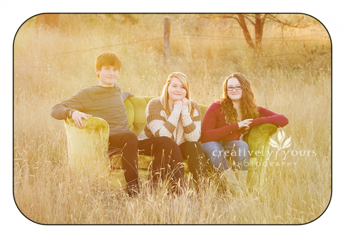 Spokane WA Sibilings photo in a field on a vintage couch by Creatively Yours Photography